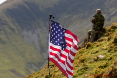 A photographer awaits aircraft low level passes in the Mach Loop, Snowdonia, Wales (LFA7) with a US flag marking his position