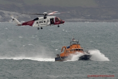 RNLI Exercise with Coastguard helicopter practicing winch transfers in Mounts Bay Cornwall